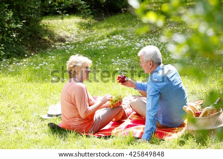 Portrait of lovely senior couple picnic outdoor and eating apple and grape.