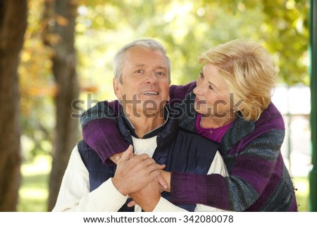 Portrait of lovely senior couple relaxing park while smiling elderly woman embracing old man.