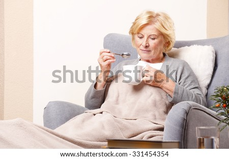 Portrait of lovely senior woman sitting at armchair at home and drinking tea. - stock photo