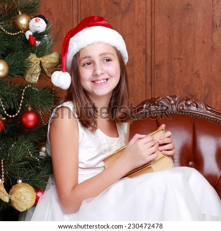 Portrait of lovely smiley brunette little girl with books on Christmas time/Charming young girl wearing cute santa hat on Holiday theme - stock photo