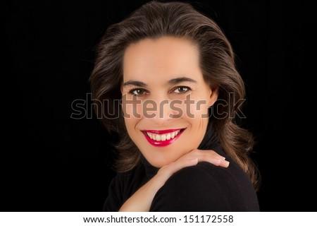 Portrait of lovely smiling mature brunette woman on black background - stock photo