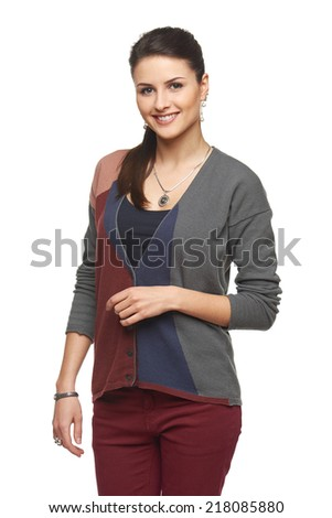 Portrait of lovely smiling young girl in cardigan looking at camera, over white background - stock photo