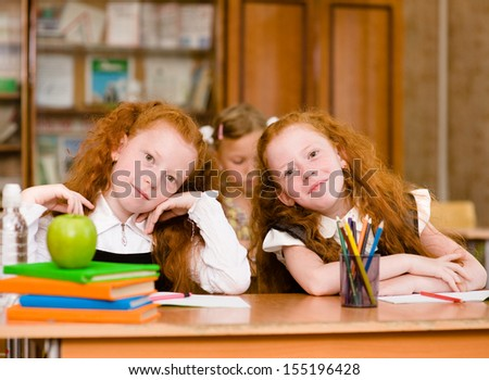Portrait of lovely twins girls with schoolboys on background. looking at camera - stock photo
