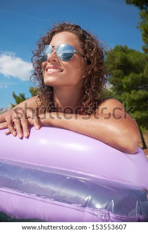 Portrait of lovely woman in bikini and sunglasses lying on mattress in sea