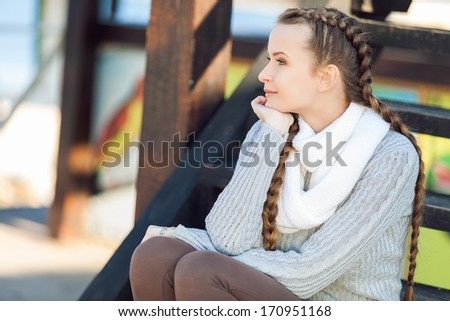 Portrait of lovely young female sitting on steps and smiling