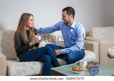 Portrait of lovely young man and woman on the couch - stock photo