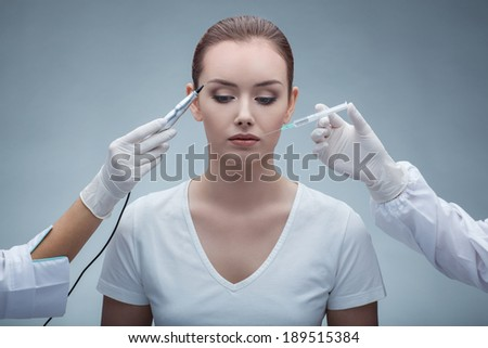 portrait of lovely young woman getting permanent makeup and  botox injection  - stock photo