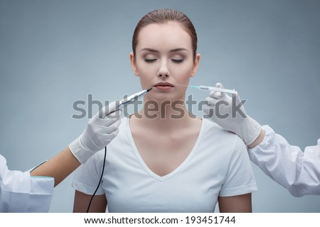 portrait of lovely young woman getting permanent makeup and collagen injection  - stock photo