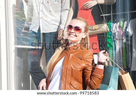 Portrait of lovely young woman smiling and carrying shopping bag near fashion shop