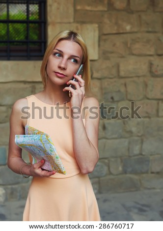 Portrait of lovely young woman talking on cell phone while standing in the city street in summer, businesswoman at telephone call, female tourist hold city map in the hand having mobile conversation