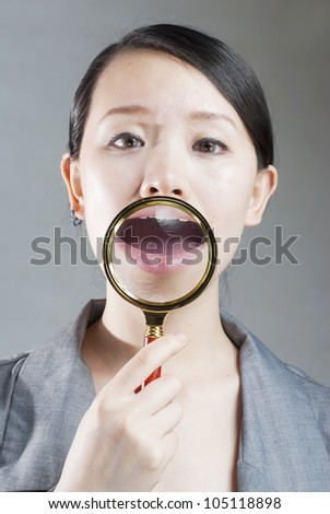 Portrait of lovely young woman with magnifying glass showing her white teeth - stock photo