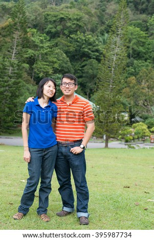 Portrait of loving Asian couple in the park - stock photo