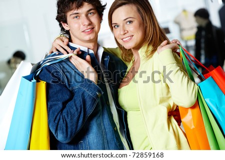 Portrait of loving couple after buying gifts looking at camera with smiles - stock photo