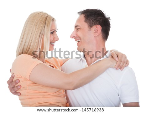 Portrait Of Loving Couple Embracing Isolated Over White Background