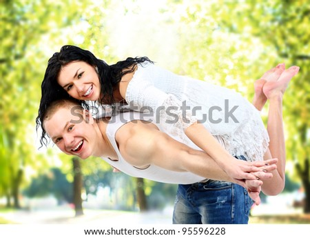 Portrait of loving couple enjoying together while piggyback ride outdoors - stock photo