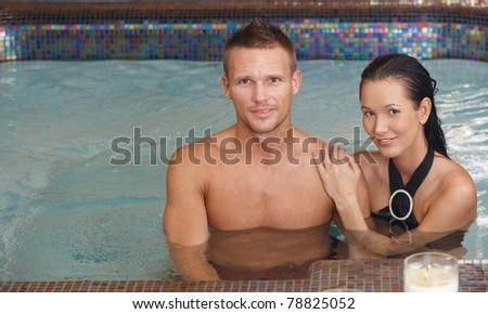 Portrait of loving couple in swimming pool, smiling at camera.? - stock photo