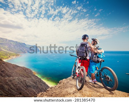 Portrait of loving couple standing on top of the mountain with bicycles.  - stock photo