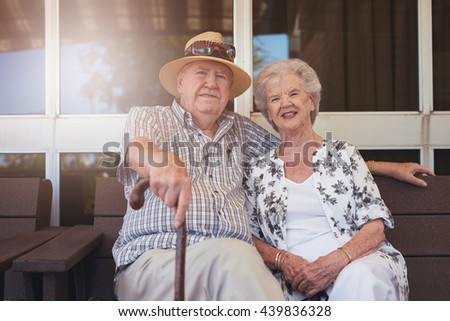 Portrait of loving elderly couple sitting on a bench outside their house. Caucasian elderly man and woman sitting relaxed on a bench outdoors. - stock photo