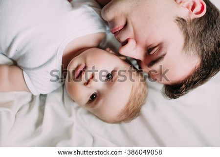 Portrait of loving father with baby boy 4-6 months his son at home on white