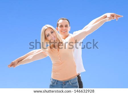 Portrait Of Loving Happy Couple Against Blue Sky - stock photo