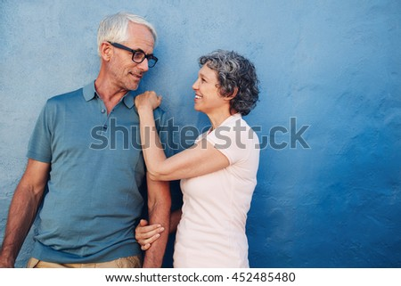 Portrait of loving mature man and woman looking at each other. Romantic couple standing together against a blue wall. - stock photo
