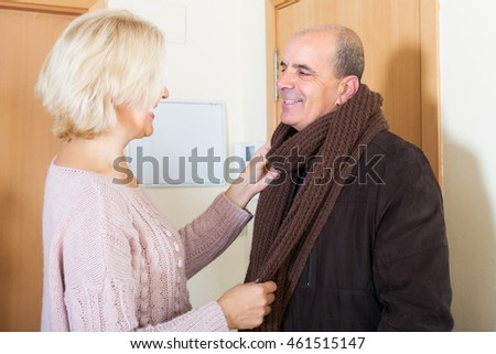 Portrait of loving mature spouses saying goodbye at doorway