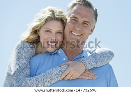 Portrait of loving mature woman embracing man from behind against clear blue sky - stock photo
