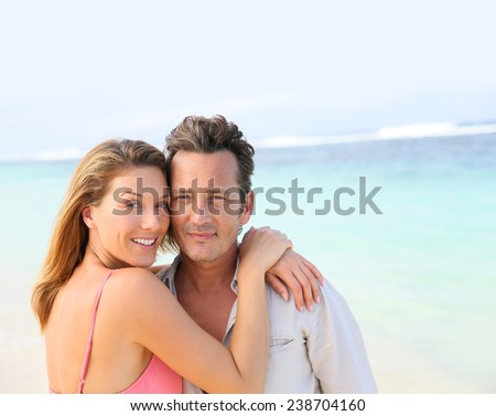 Portrait of loving middle-aged couple at the beach - stock photo