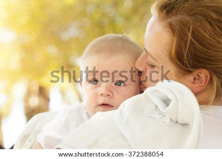 Portrait of loving mother hugging her baby outdoors - stock photo