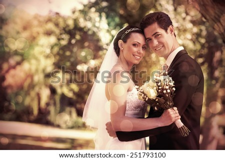 Portrait of loving newly wed couple with head to head standing in garden - stock photo