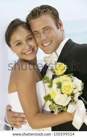 Portrait of loving newlywed couple standing cheek to cheek outdoors - stock photo