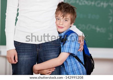 Portrait of loving schoolchild hugs his mother after school - stock photo