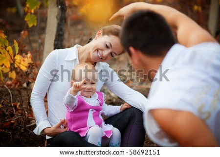Portrait of loving young parents walking with their baby in autumn park - stock photo