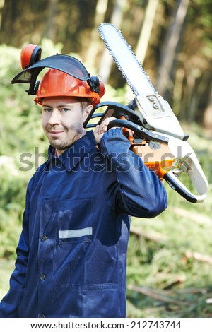 Portrait of lumberjack logger worker in protective workwear with chainsaw at forest - stock photo