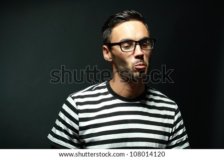 portrait of  macho man in glasses and pursing his lips black background - stock photo