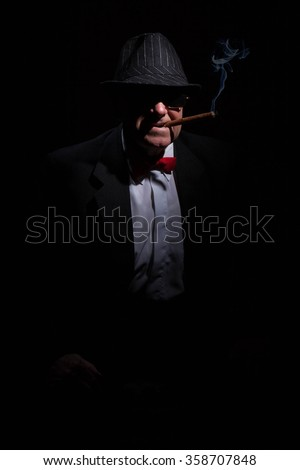 Portrait of mafia boss with cigar and glasses. - stock photo