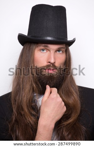 Portrait of magician with long hair and moustache. Serious man posing in photostudio.