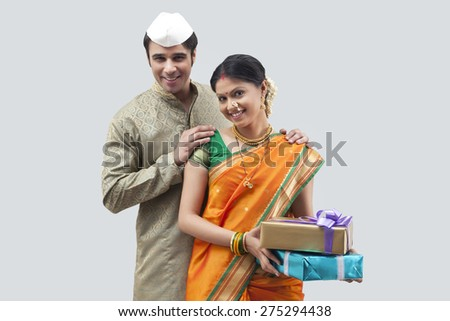 Portrait of Maharashtrian couple holding gifts - stock photo