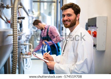 Portrait of maintenance workers examining brewery machine at brewery factory