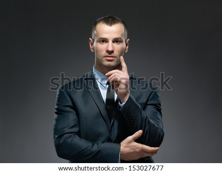 Portrait of making forefinger gesture businessman wears business suit and black tie