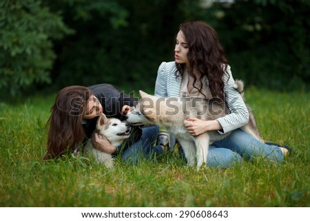 portrait of malamutes puppies and beautiful girls