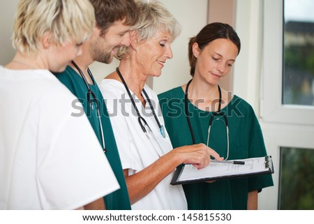 Portrait of male and female doctors reading report in hospital - stock photo