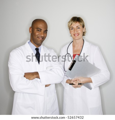 Portrait of male and female doctors standing smiling. - stock photo