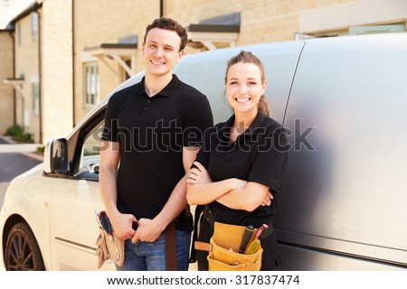 Portrait of male and female trade workers by a van - stock photo