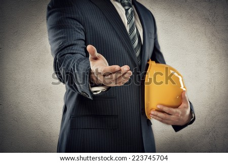 Portrait of male architect with safety hardhat greeting his partner. Young man builder showing handshake. Partnership concept.   - stock photo