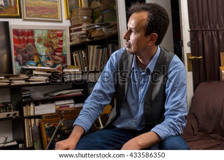 Portrait of male artist sitting looking trough his studio with a paint brush and rag in his hand with a dejected expression as though not happy with the result - stock photo