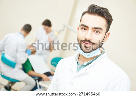 Portrait of male asian dentist wearing lab coat while sitting in clinic - stock photo