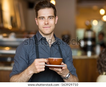 Portrait of male barista standing in cafe with cup of coffee - stock photo