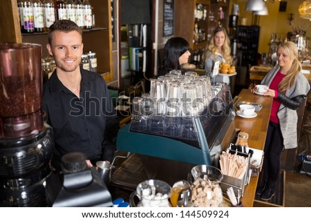 Portrait of male bartender with colleague working in background at cafe - stock photo
