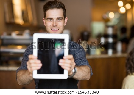 Portrait of male cafe owner holding digital tablet in restaurant - stock photo